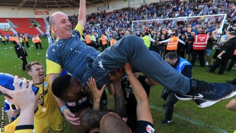 Wigan boss Paul Cook celebrates winning the League One title