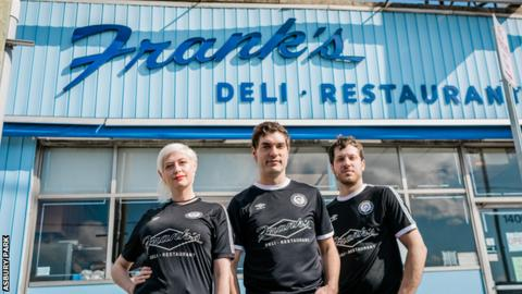 Members of band Dentist pose in Asbury Park kits in front of Frank's Deli, a New Jersey staple visited by Anthony Bourdain in his 2015 episode of Parts Unknown spotlighting the Jersey shore. The club is donating proceeds of sales of this shirt into Frank's tip jar.