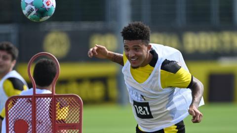 Jadon Sancho heads the ball in training