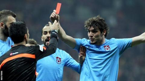 Salih Dursun (right) waves a red card at referee Deniz Bitnel