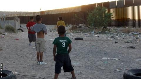 Kids play football by US border in Ciudad Juarez