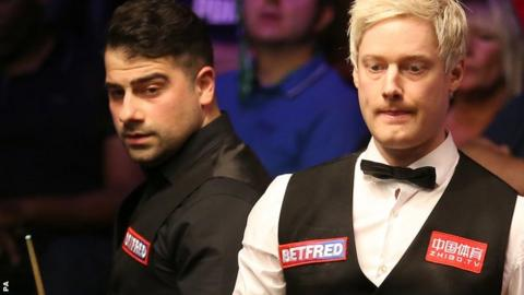 Neil Robertson (right) is watched by Michael Georgiou