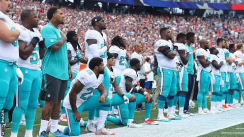 Miami Dolphin players kneel during the US national anthem