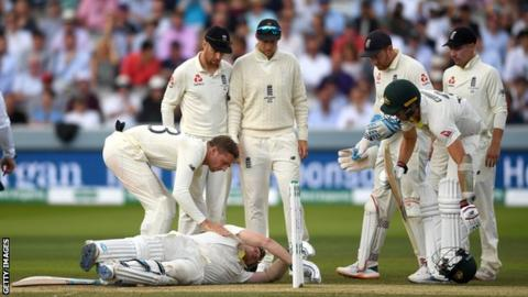England players check on Australia batsman Steve Smith after he is hit in the neck by a Jofra Archer bouncer