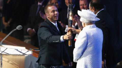 Sir Chris Hoy presents Commonwealth Games Federation president Prince Imran the baton as the Queen looks on