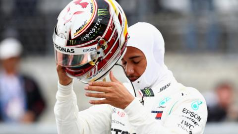 Lewis Hamilton takes of his crash helmet