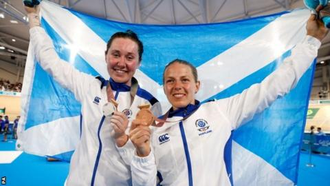 Katie Archibald and Neah Evans hold the Scotland flag aloft after winning silver and bronze medals in the women's points race