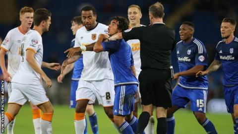 Fabio Da Silva of Cardiff City is restrained by players and the referee as he challenges Alex Bruce of Hull City