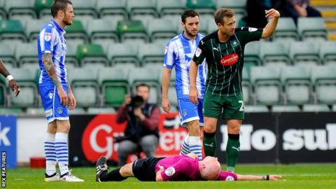 Plymouth Argyle's David Fox waves the physio on after a collision between referee Kevin Johnson and Jimmy Spencer