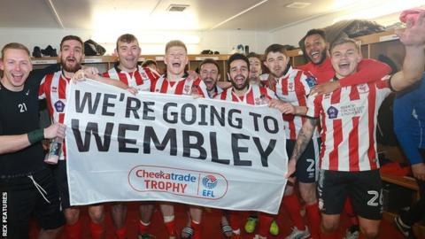 Lincoln City players celebrate beating Chelsea Under-21s on penalties in the EFL Trophy