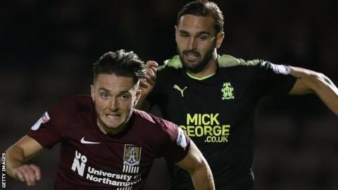 Greg Taylor (right) chases Northampton midfielder Matt Grimes