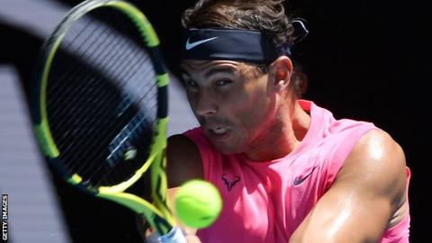 Rafael Nadal in close-up, watching the ball off his racquet as he plays a shot