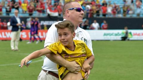 A young fan is restrained after running onto the pitch to get a photograph with Christian Pulisic after Borussia Dortmund's pre-season win over Liverpool