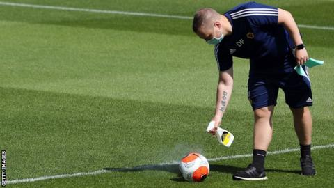 A member of staff sprays a ball with disinfectant