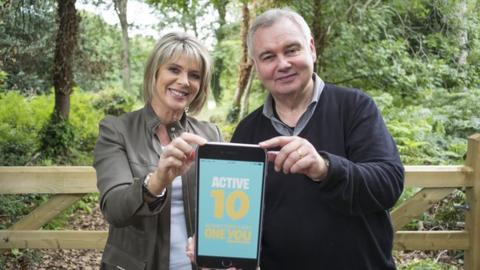 Ruth Langford and Eamonn Holmes holding a large iphone and smiling