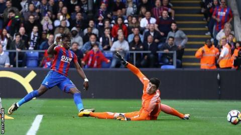 Wilfried Zaha scores past Chelsea's Thibaut Courtois to give Crystal Palace their first Premier League win of the season