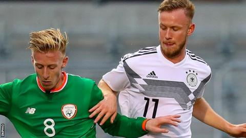 Henry Charsley of the Republic of Ireland in action against Germany's hat-trick scorer Cedric Teuchert