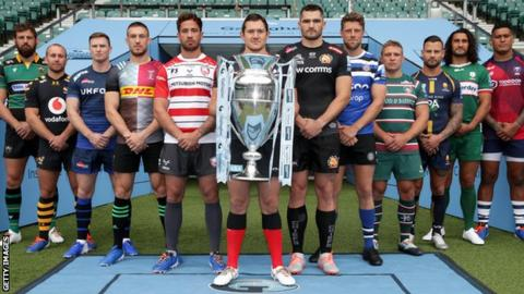 A player from each of the 12 clubs poses with the Premiership tophy