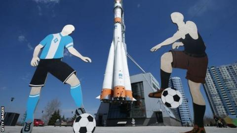 Two cut-out footballers by the Soyuz carrier rocket monument in Samara