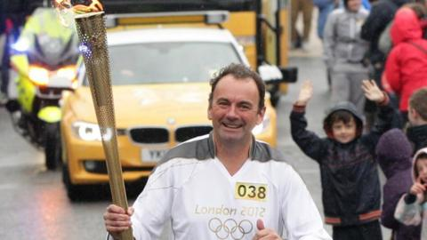 Stephen Martin carries the Olympic Flame in the Torch Relay for the 2012 London Games