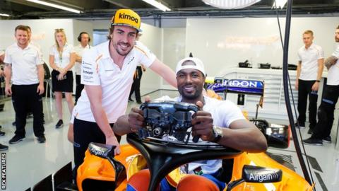 Spaniard Serge Ibaka Congolause of the NBA's Toronto Raptors tries the seat in the car of Fernando Alonso