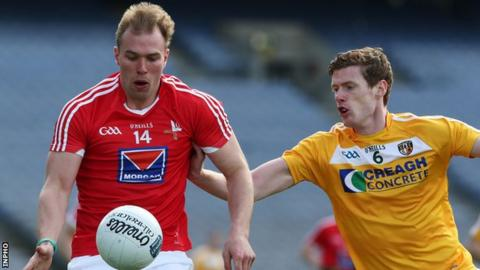 Louth's Conor Grimes is challenged by Antrim's Martin Johnston