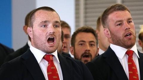 Ken Owens (L) sings on arrival in New Zealand