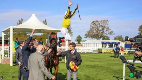 Frankie Dettori jumps off James Garfield after winning The Dubai Duty Free Mill Reef Stakes Race run at Newbury Racecourse