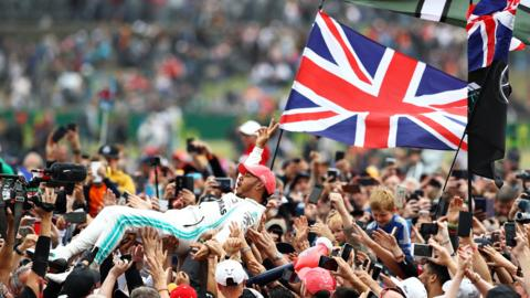 14th July 2019; Silverstone Circuit, Northampton, England; FIA F1 Grand Prix of Britain, Race Day; Mercedes AMG Petronas Motorsport driver Lewis Hamilton celebrates his win with the fans (photo by Tim Williams/Action Plus via Getty Images)