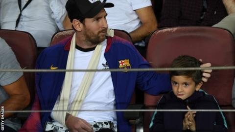 Lionel Messi watching a Barcelona game with his son