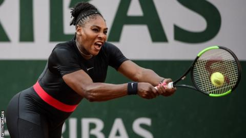 Serena Williams plays a backhand while wearing a black catsuit at the French Open