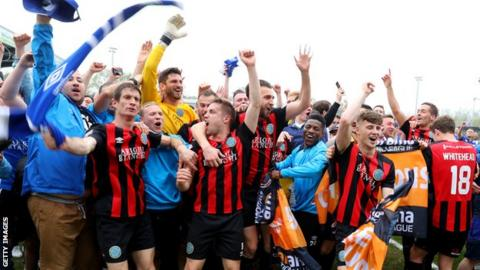 Macclesfield Town players and fans celebrate their promotion at the final whistle