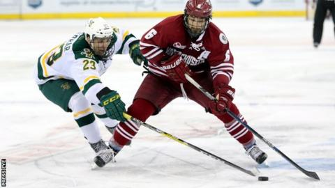 Vermont's Rob Darr tussles for the puck with Umass opponent Dominic Trento in the Friendship Four