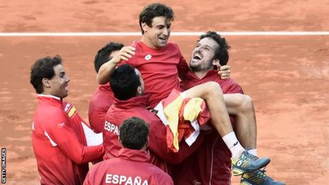 Spain's David Ferrer is held up by his team-mate after victory in the Davis Cup