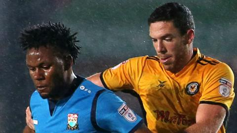 Shaquile Coulthirst of Barnet is challenged by Ben Tozer of Newport County
