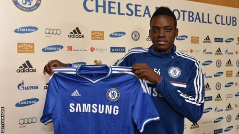 Bertrand Traore holding a Chelsea shirt after signing in 2014