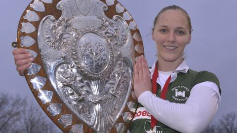 Randalstown captain Shelley Black lifts the Ulster Shield after her team's 4-2 penalty shoot-out win over Queen's University after the final at Stormont had ended in a 2-2 draw