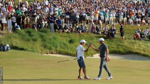 Brooks Koepka celebrates with caddy Ricky Elliott on the 18th green at Shinnecock Hills