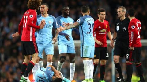 Marouane Fellaini gestures with his palms facing outwards as he stands over the fallen Sergio Aguero
