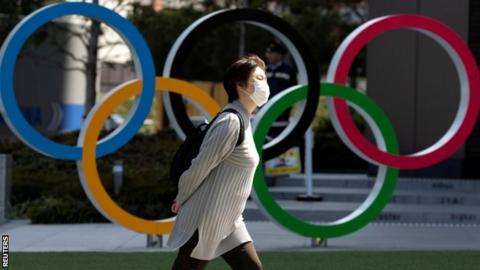 A woman wearing a protective mask walking in front of Olympic rings at the Olympics Museum in Tokyo