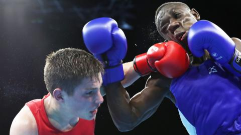 Thomas Blumenfeld of Canada (red) and Jessie Lartey of Ghana (blue) compete in their men's light welter semi-final