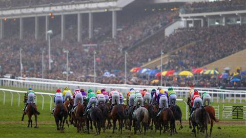 The crowd watch the horses going to post for the first race on the final day of the Cheltenham Festival horse racing meet at Cheltenham Racecourse in Gloucestershire, south-west England, on March 16, 2018