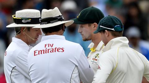 Umpires Nigel Llong and Richard Illingworth speak to Australia's Cameron Bancroft (second right) and captain Steve Smith