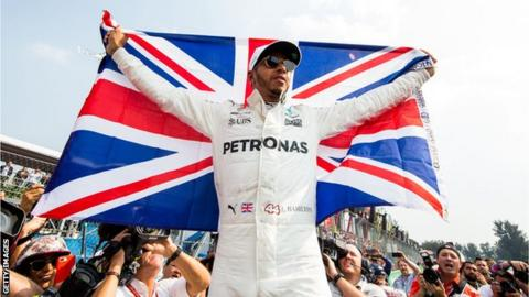 Lewis Hamilton holding a Union Jack flag after winning the drivers' title in Mexico in 2017