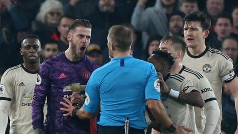 Manchester United keeper David De Gea confront referee Craig Pawson during his side's defeat at Liverpool