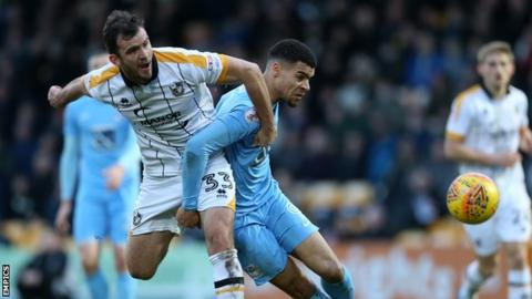 Port Vale defender Gavin Gunning challenges for the ball with Coventry City's Max Biamou