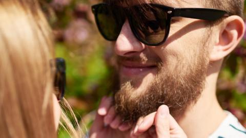 Woman strokes a man's beard