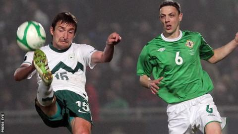 Slovenia's Armin Bacinovic comes under pressure from Chris Biard in the Euro 2012 qualifier in Belfast