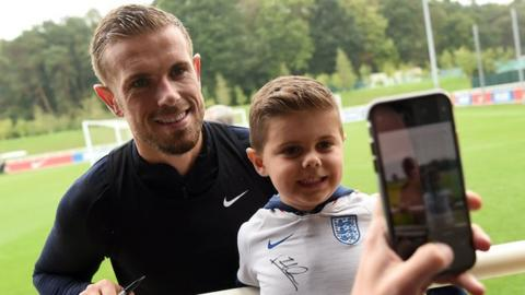 Jordan Henderson poses for a photo with a young England fan