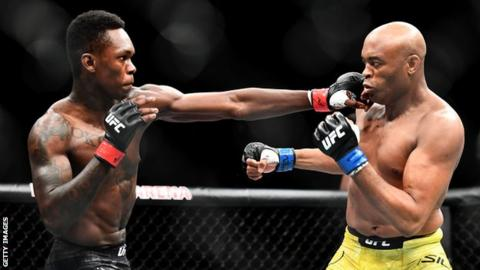 Israel Adesanya (left) aims a blow at Anderson Silva